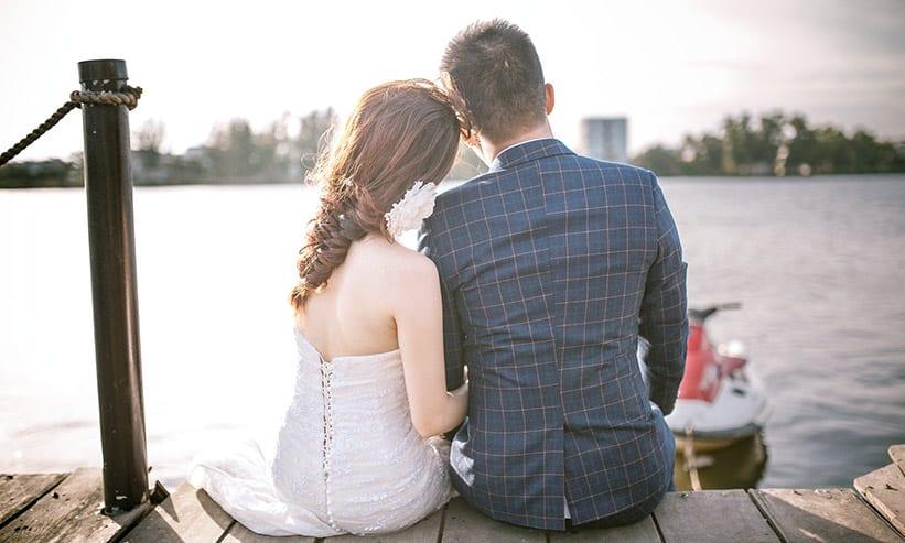 湖のほとりで座っているカップルの後ろ姿