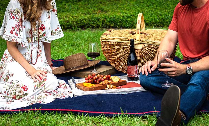 外でレジャーシートに座りワインを飲むカップル