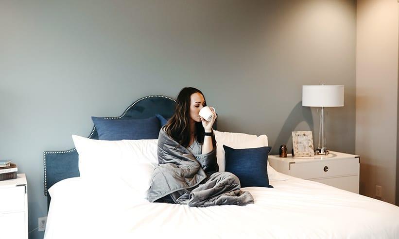 毛布をかけてベッドでコーヒーを飲む女性