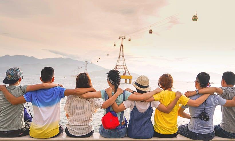 座って海を見ながら肩を組んでいる男女