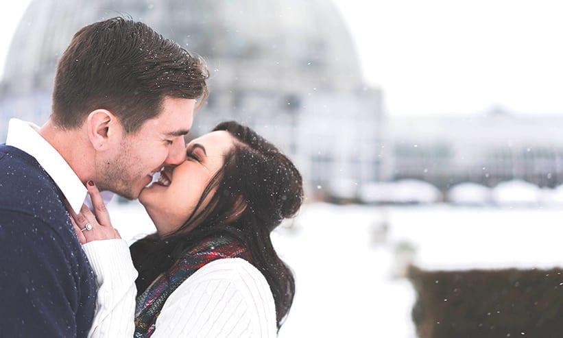 雪が降る中キスをするカップル