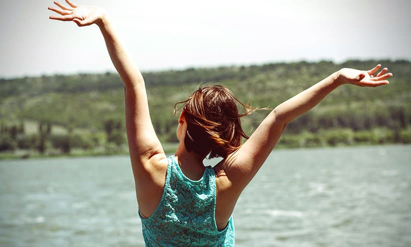 湖で両手をあげている女性の後ろ姿