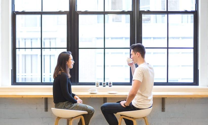 カフェでコーヒーを飲みながら見つめ合うカップル