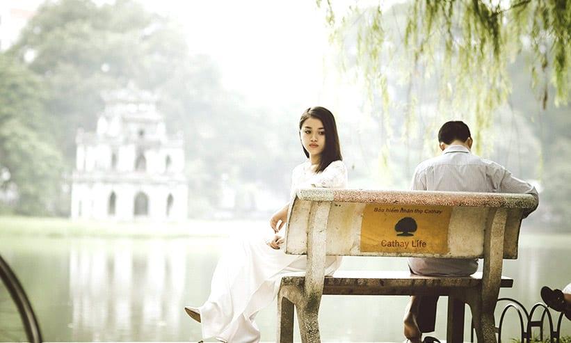 湖のベンチに座るカップル