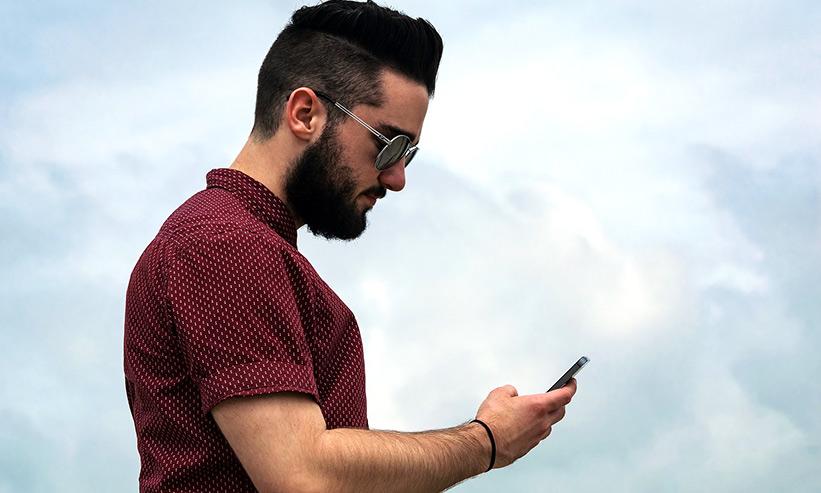 スマートフォンを見るサングラスをかけた男性