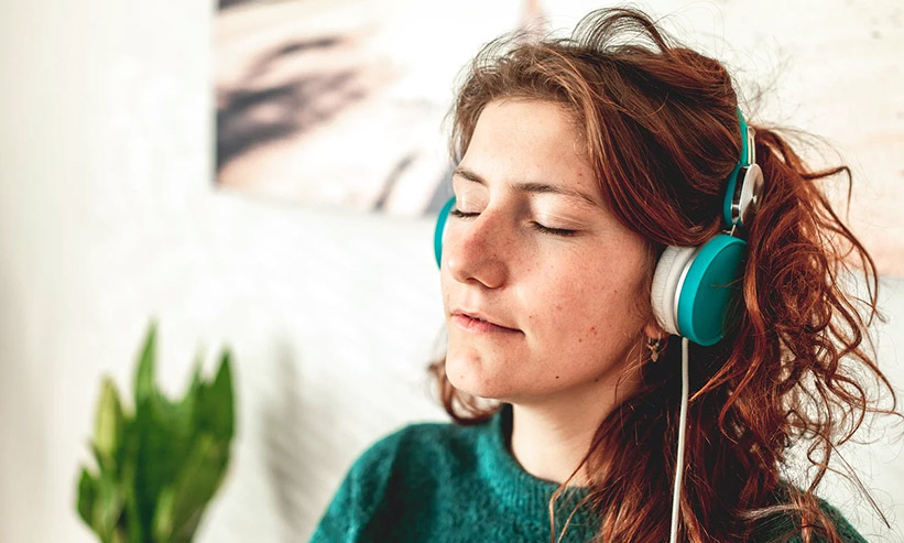 目を閉じ音楽を聴く女性