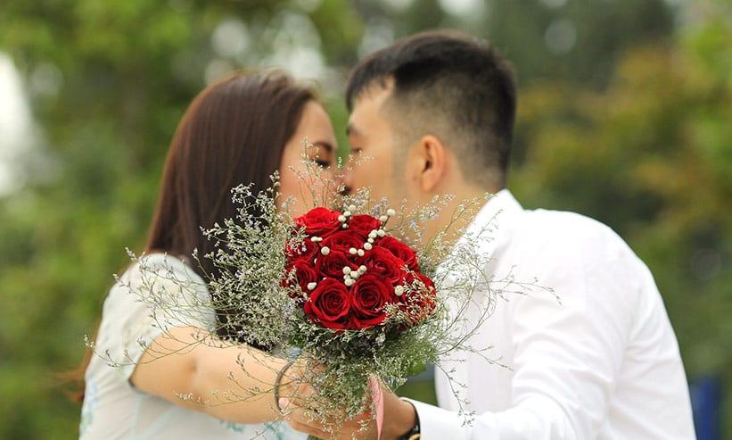 花束を持ちキスをするカップル