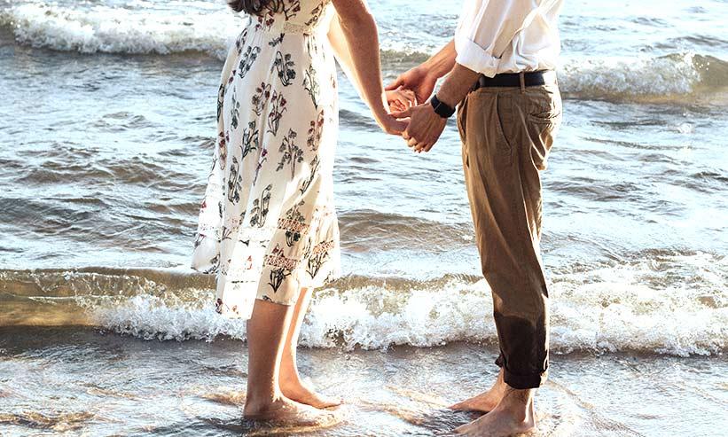 波打ち際で手を取り合うカップル