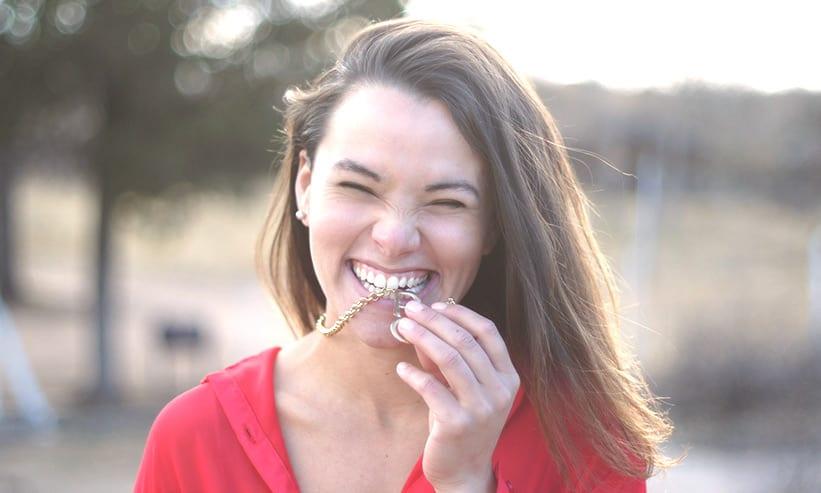 笑いながらネックレスを噛む女性