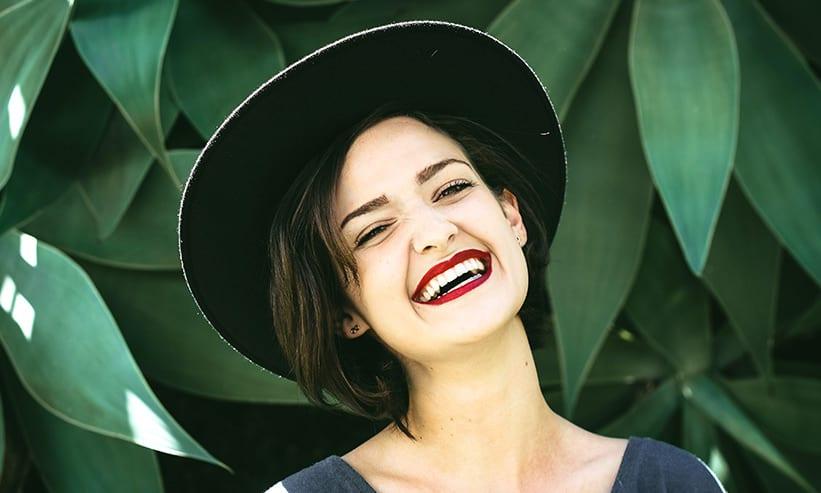 黒のハットを被りニッコリ笑っている女性