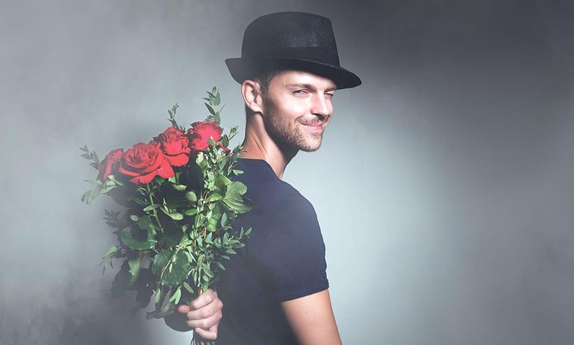 赤い薔薇の花束を背中に隠す男性