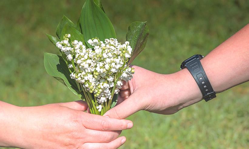 女性に白い花のブーケを渡す男性