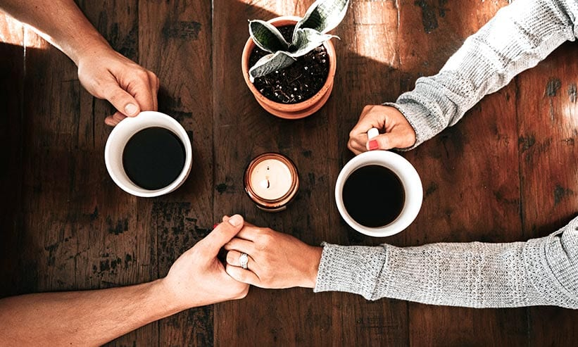 コーヒーを飲みながら手を繋ぐカップル
