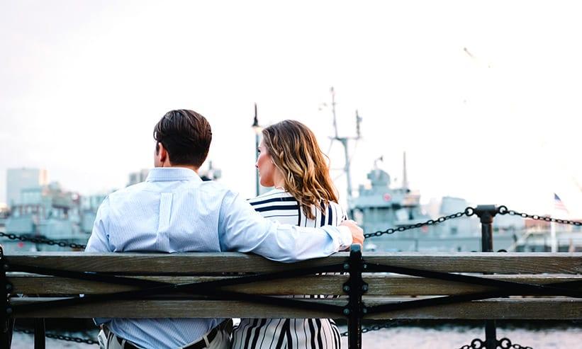 ベンチに座り女性の肩に腕を回す男性
