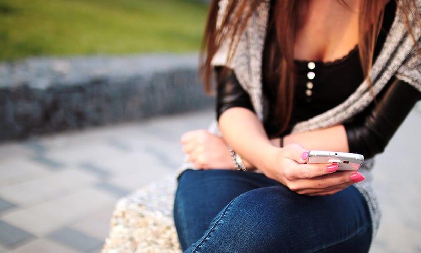 座ってスマートフォンを操作する女性
