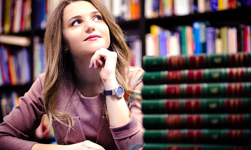 図書館で上を向いて考える女性