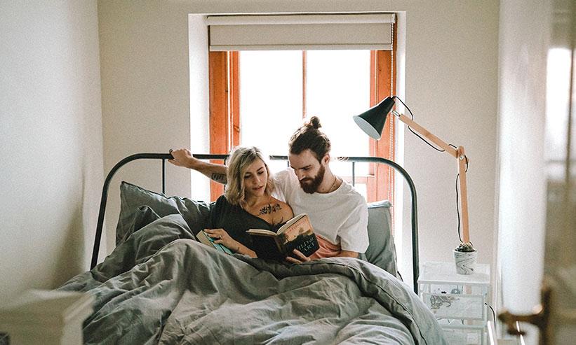 ベッドで一緒に本を読むカップル