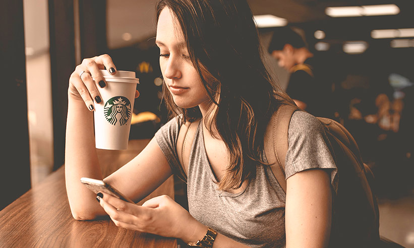 カフェでコーヒーを飲みながらスマートフォンを見る女性