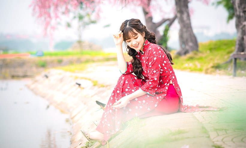 川のほとりで座っている女性