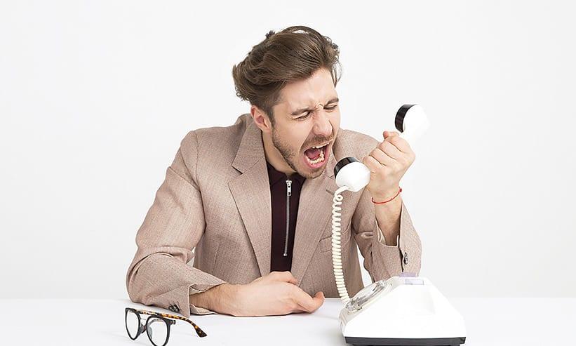 受話器に向かって叫ぶ男性