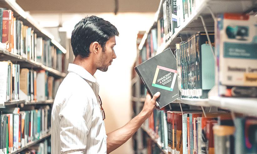 図書館で本を取る男性