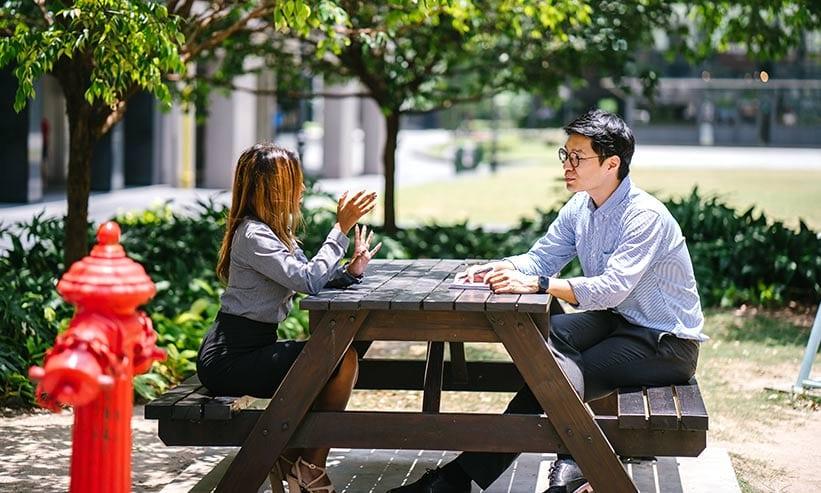 公園のベンチで話をする男女