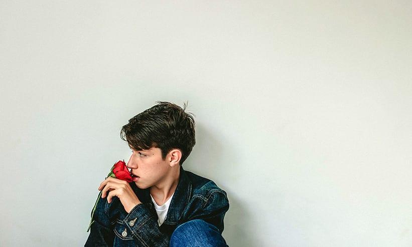 座って赤い薔薇の匂いを嗅ぐ男性