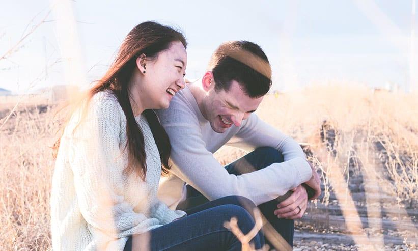 草原に座り楽しそうに話をしているカップル