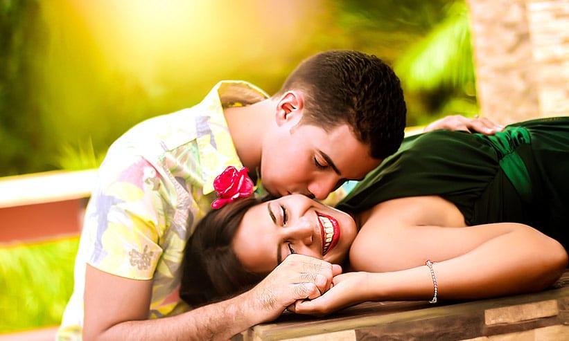 寝転んでいる女性の頬にキスをする男性
