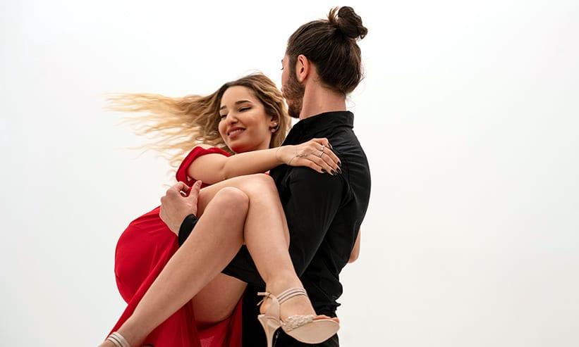 赤いドレスの女性をお姫様抱っこしている男性