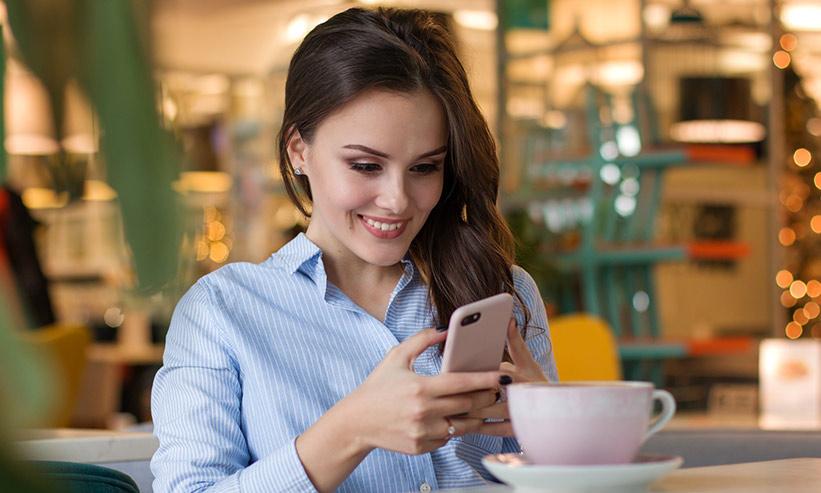 カフェでスマートフォンを見ている女性