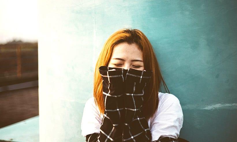 口を手で塞いで目を閉じている女性