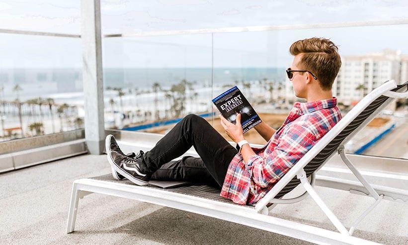 テラスで椅子に座って本を読む男性