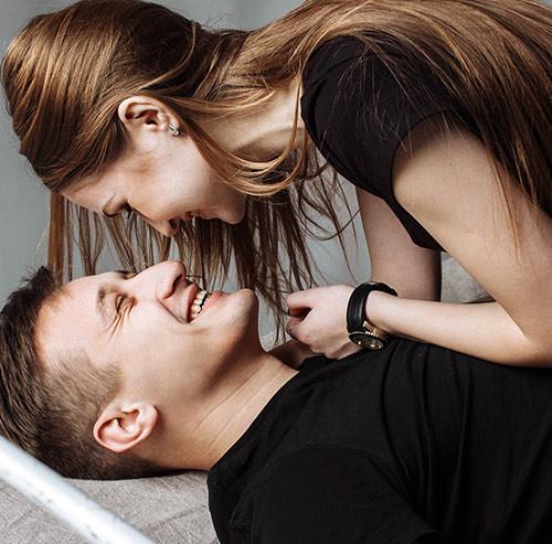 横になり見つめ合うカップル