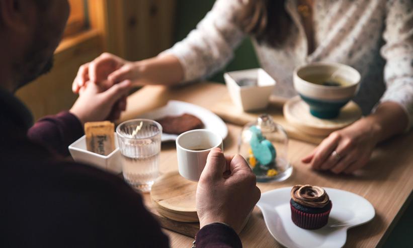 コーヒーを飲みながら手を取り合うカップル