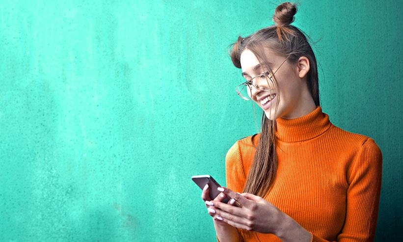 笑いながらスマートフォンを見る女性