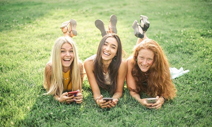 寝転んで楽しそうに笑う3人の女性