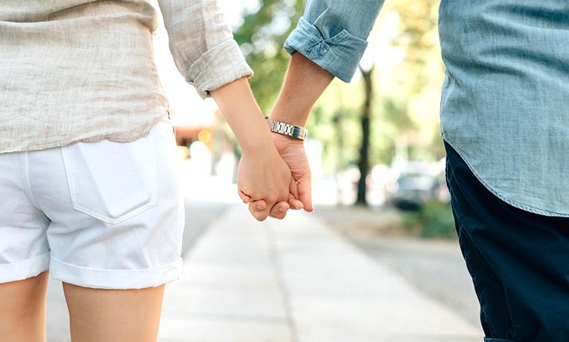 手を繋ぐカップルの後ろ姿