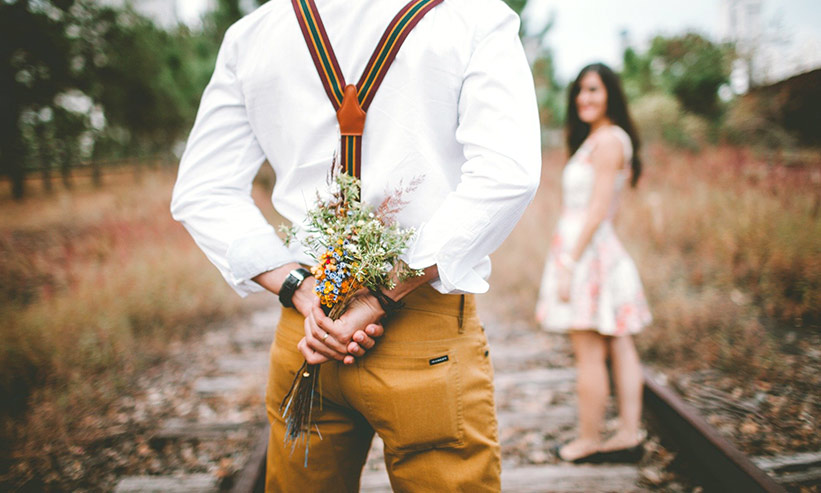 花束を後ろに隠し持つ男性