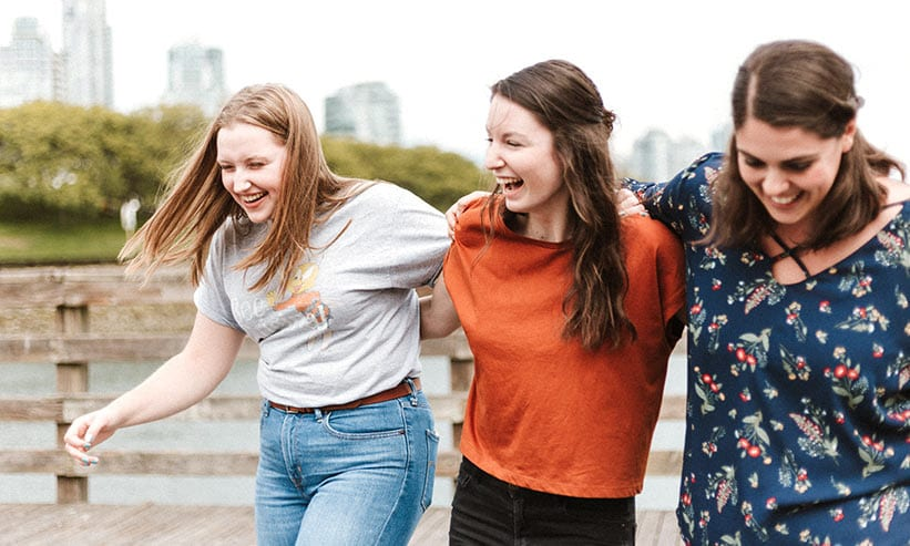 笑いながら肩を組む3人の女性