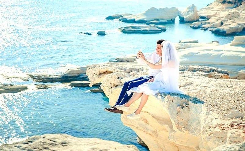 崖に座って写真をとるカップル