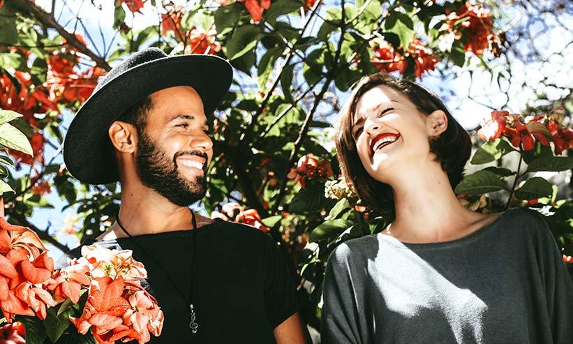 植物が生茂る中笑い合うカップル
