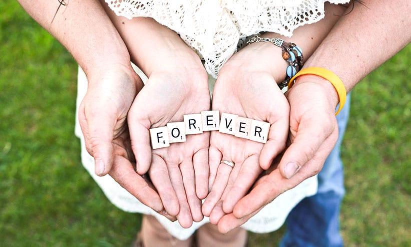 FOREVERのタイルを2人で持っているカップルの手