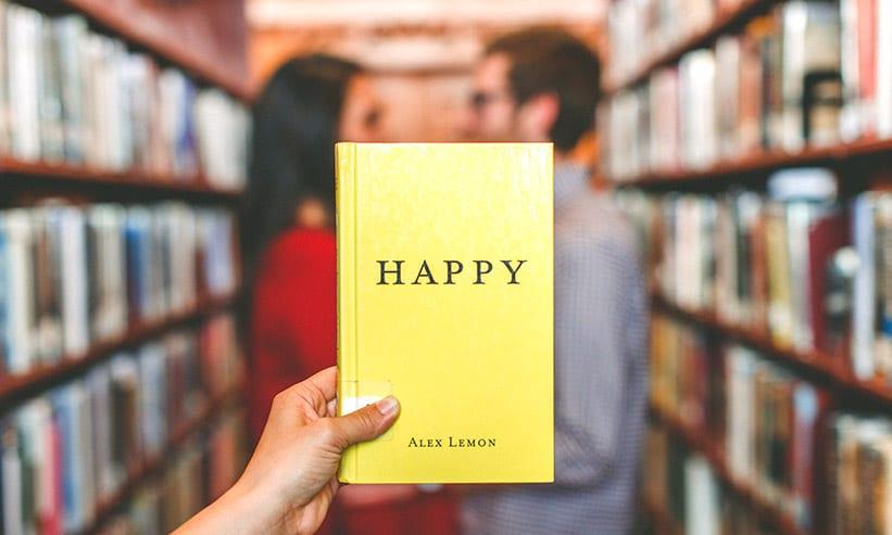 HAPPYと書かれた黄色い本を持つ女性