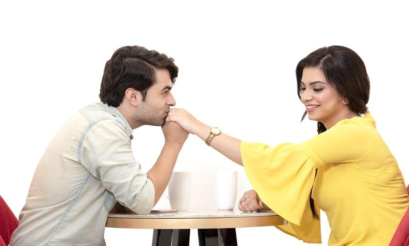 カフェで女性の手にキスをする男性