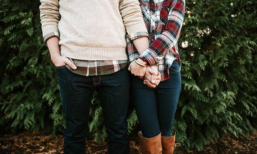 手を握り合い寄り添って立っているカップル
