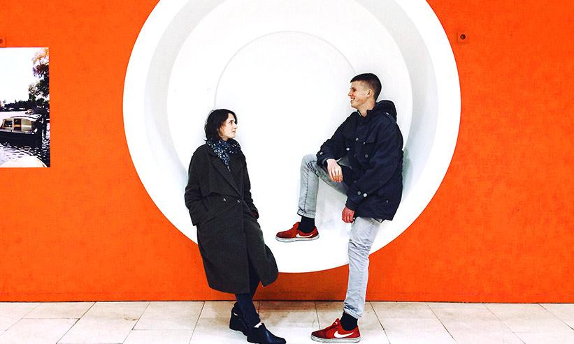赤い壁に埋め込まれた丸いオブジェに腰掛けるカップル