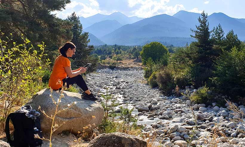 河原でタブレッドを見る女性
