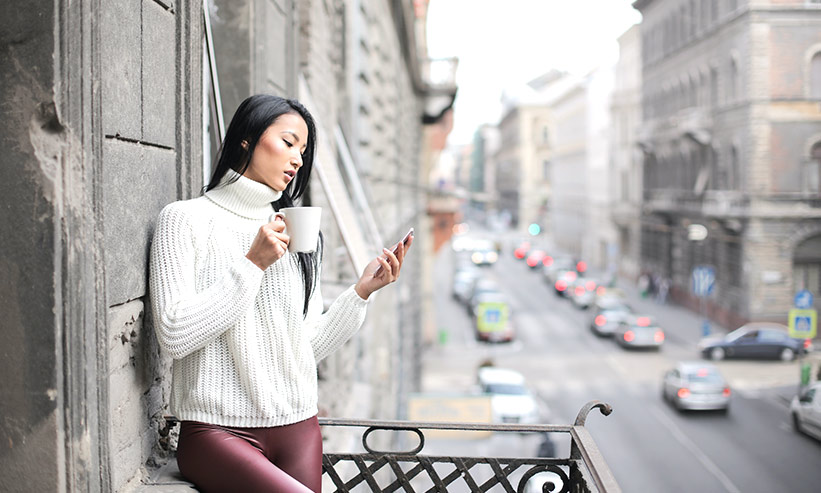 コーヒーを飲みながらスマートフォンを見る女性