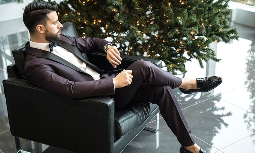 椅子に座って時計を確認するスーツ姿の男性